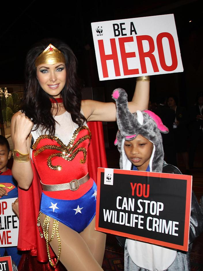 """Miss Universe 2005 Natalie Glebova of Canada, wearing Wonder Woman costume poses with Thai children during Convention on International Trade in Endangered Species, or CITES, in Bangkok, Thailand Sunday, March 3, 2013. How to slow the slaughter and curb the trade in """"blood ivory"""" will be among the most critical issues up for debate at the 177-nation Convention on International Trade in Endangered Species, or CITES, that gets under way Sunday in Bangkok. And the meeting's host, Thailand, will be under particular pressure to take action. (AP Photo/Sakchai Lalit)"""