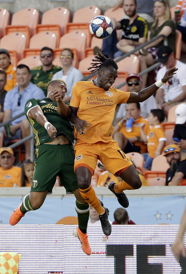 Portland Timbers defender Bill Tuiloma (25) and Houston Dynamo forward Alberth Elis (17) both go up for a head ball during the first half of an MLS soccer match Wednesday, May 15, 2019, in Houston. (AP Photo/Michael Wyke)