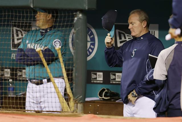 Seattle Mariners manager Eric Wedge, right, puts his cap on in the dugout during ceremonies before a baseball game against the Oakland Athletics, Friday, Sept. 27, 2013, in Seattle. Before the game, Wedge announced that he would not be returning to manage the Mariners next season. (AP Photo/Ted S. Warren)