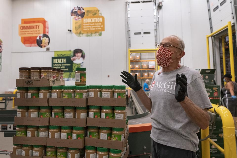 Volunteer Rob Britton, of Washington, finishes stacking peanut butter as boxes of food are packed for distribution, at The Capital Area Food Bank, Tuesday, Oct. 5, 2021, in Washington. (AP Photo/Jacquelyn Martin)