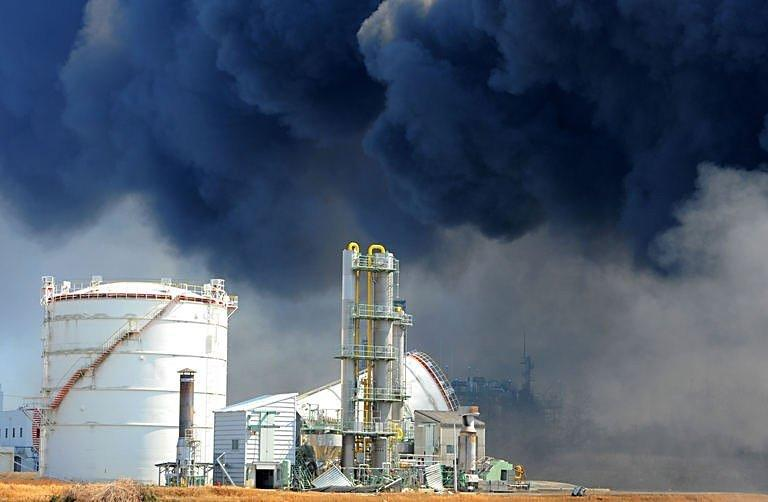 Smoke billows from fires raging at the port in Tagajo, Miyagi prefecture