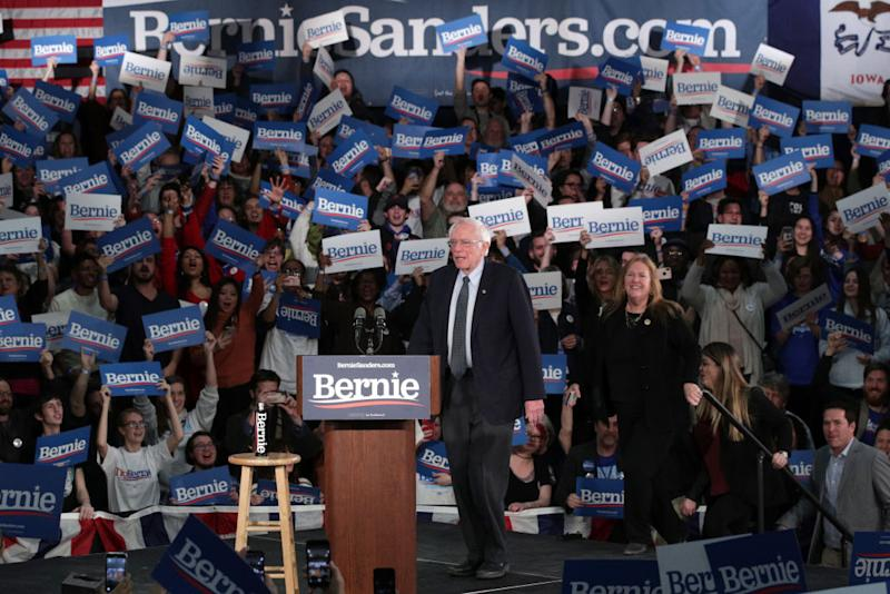 Bernie Sanders seen on stage with supporters in background.