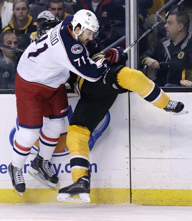 Columbus Blue Jackets left wing Nick Foligno (71) checks Boston Bruins center Patrice Bergeron (37) against the boards during the first period of an NHL hockey game, in Boston, Thursday, Nov. 14, 2013. (AP Photo/Charles Krupa)