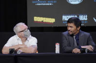 Manny Pacquiao, right, of the Philippines, looks at his trainer Freddie Roach during a news conference Wednesday, Aug. 18, 2021, in Las Vegas. Pacquiao is scheduled to fight Yordenis Ugas, of Cuba, in a welterweight championship bout Saturday in Las Vegas. (AP Photo/John Locher)