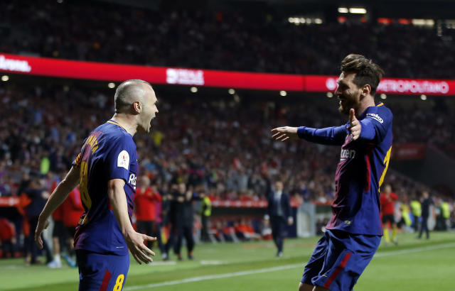 Barcelona's Andres Iniesta, left,, celebrates with Lionel Messi after scoring his side's fourth goal during the Copa del Rey final soccer match between Barcelona and Sevilla at the Wanda Metropolitano stadium in Madrid, Spain, Saturday, April 21, 2018. (AP Photo/Paul White)