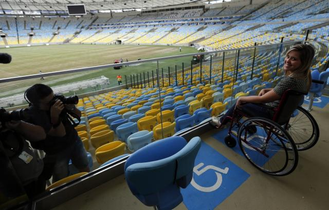 A woman simulates a using a wheelchair at a physically handicapped lot inside of the Maracana stadium, one of the stadiums hosting the 2014 World Cup soccer matches, during a press visit in Rio de Janeiro, May 26, 2014. REUTERS/Sergio Moraes (BRAZIL - Tags: SPORT SOCCER WORLD CUP)