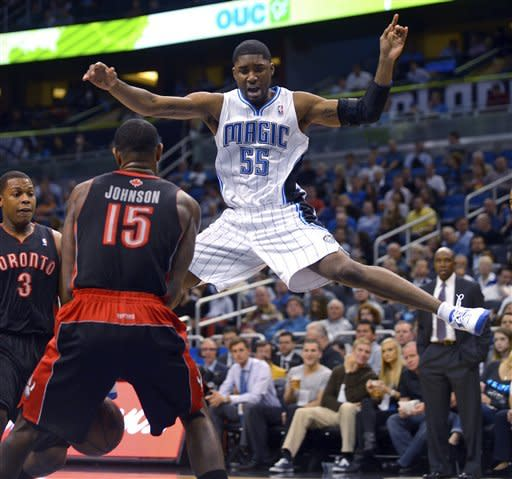 Orlando Magic guard E'Twaun Moore (55) loses control of the ball between Toronto Raptors guard Kyle Lowry (3) and Amir Johnson (15) during the first half of an NBA basketball game in Orlando, Fla., Thursday, Jan. 24, 2013.(AP Photo/Phelan M. Ebenhack)
