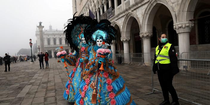 A policewoman wearing a protective mask stands next to carnival revellers at Venice Carnival, which the last two days of, as well as Sunday night's festivities, have been cancelled because of an outbreak of coronavirus, in Venice, Italy February 23, 2020.