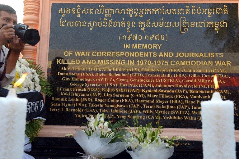 A Cambodian photographer takes a picture next to a memorial in Phnom Penh, on February 6, 2013