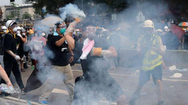 PHOTO:A demonstrator throws a canister of tear gas back towards the police outside the Legislative Council in Hong Kong, June 12, 2019. (Kin Cheung/AP)