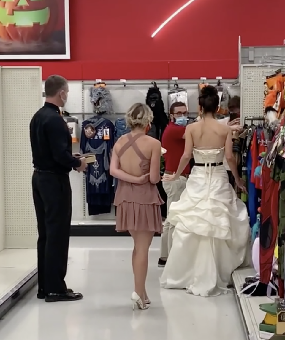 A woman dressed in a wedding dress has been caught on camera storming into a Target store, demanding her fiancé who works in the store marry her there and then or she'll break up with him. Photo: TikTok/@boymom_ashley