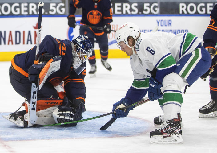Edmonton Oilers goalie Mike Smith (41) makes a save on Vancouver Canucks' Brock Boeser (6) during the first period of an NHL hockey game Saturday, May 8, 2021, in Edmonton, Alberta. (Jason Franson/The Canadian Press via AP)