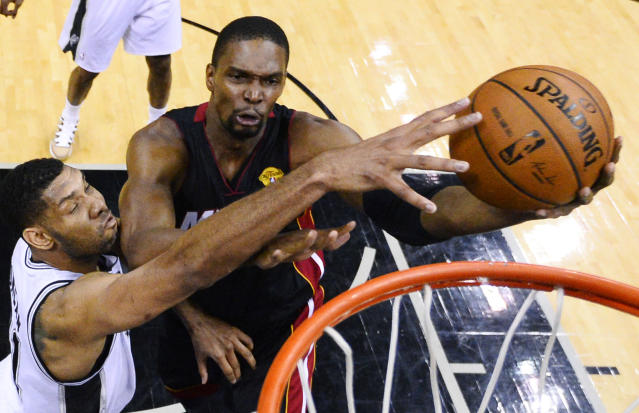 Miami Heat center Chris Bosh shoots as San Antonio Spurs forward Tim Duncan, left, defends during the first half in Game 2 of the NBA basketball finals on Saturday, Nov. 8, 2014, in San Antonio. (AP Photo/Larry W. Smith, pool)