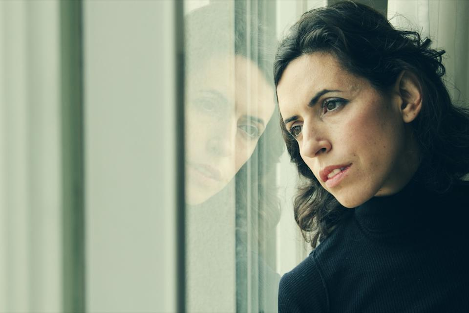 Woman looking out window during a lockdown