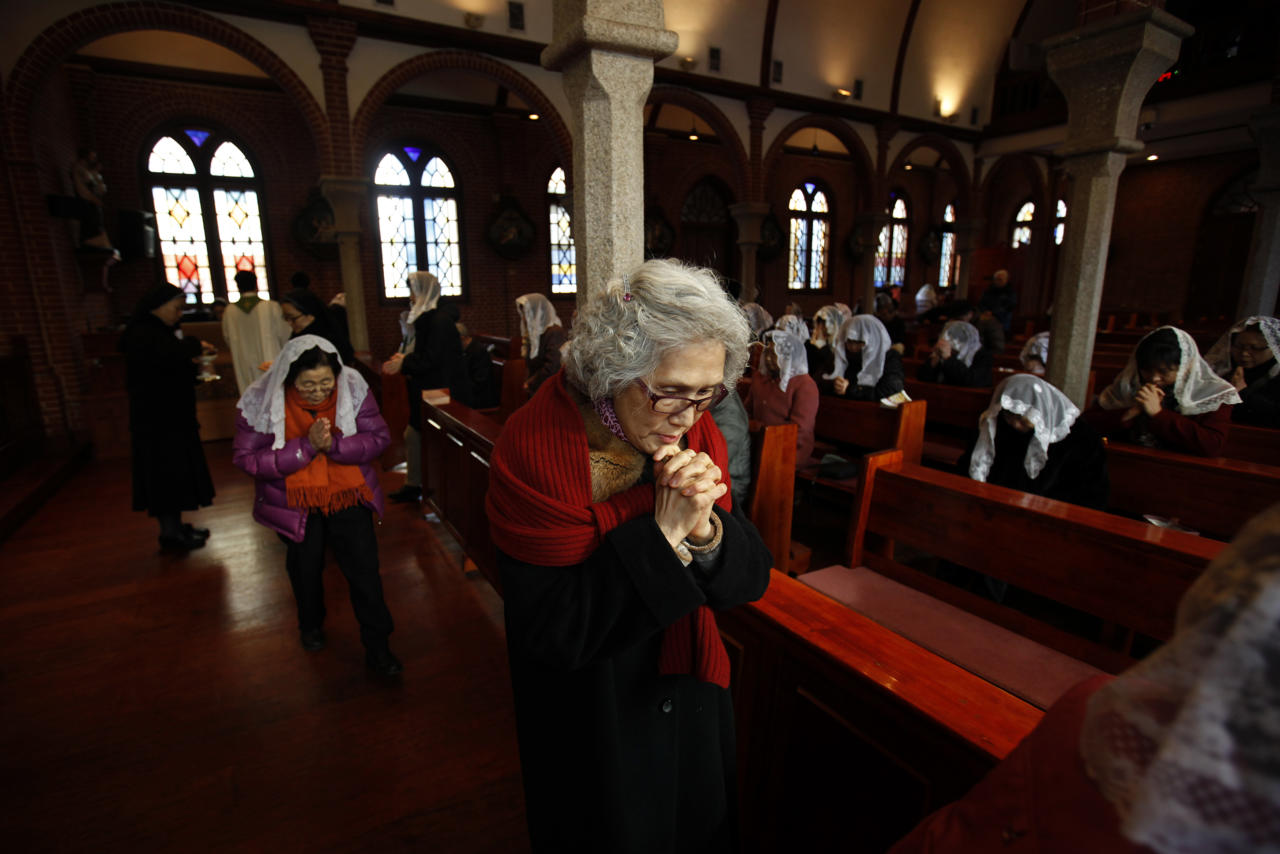 A woman prays during a mass at a catholic church in Seoul February 12, 2013. Pope Benedict left the Catholic world in shock after becoming the first pontiff since the Middle Ages to resign his office, saying that failing strength had left him unable to lead the church through a period of relentless change and turmoil.   REUTERS/Kim Hong-Ji (SOUTH KOREA - Tags: RELIGION) - RTR3DNXU