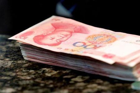 FILE PHOTO: Chinese 100 yuan banknotes are seen on a counter of a branch of a commercial bank in Beijing