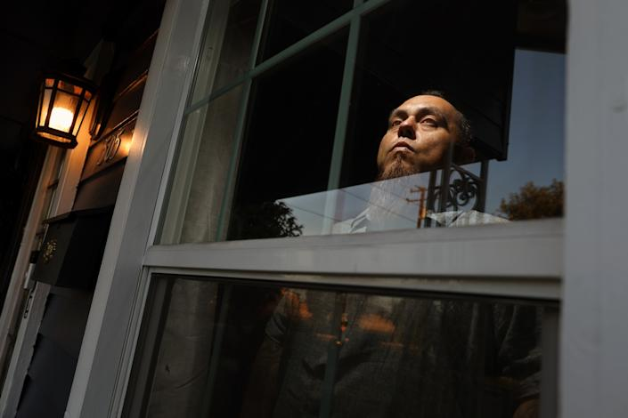 """Rafael Saavedra at his home in Alhambra. The truck driver, whose pay has been cut in half, fears infecting his daughters at home. <span class=""""copyright"""">(Gary Coronado / Los Angeles Times)</span>"""