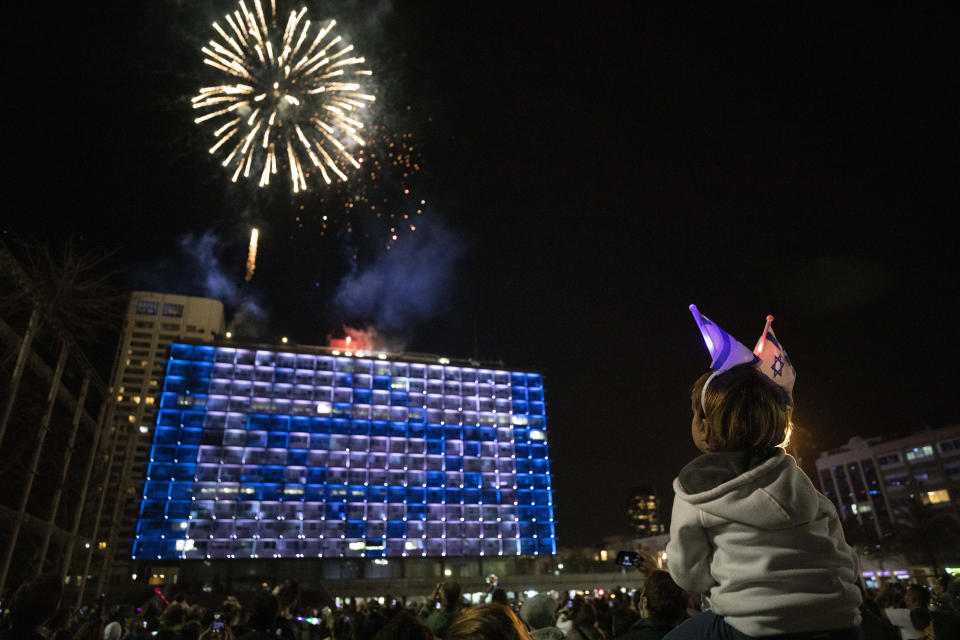 Israelis watch a fireworks show during Israel's Independence Day celebrations after more than a year of coronavirus restrictions in Tel Aviv, Israel, Wednesday, April 14, 2021. (AP Photo/Sebastian Scheiner)