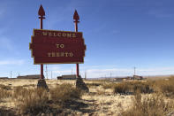 A handcrafted sign welcomes people to the community of Teesto, Ariz., on Feb. 11, 2021. Teesto workers, health representatives, volunteers and neighbors keep close tabs on another to ensure the most vulnerable citizens get the help they need. (AP Photo/Felicia Fonseca)