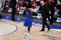 Dallas Mavericks guard Luka Doncic (77) pulls his jersey over his face after attempting a final-second shot that he did not make as San Antonio Spurs head coach Gregg Popovich, right rear, looks on during an NBA basketball game in Dallas, Sunday, April 11, 2021. (AP Photo/Tony Gutierrez)
