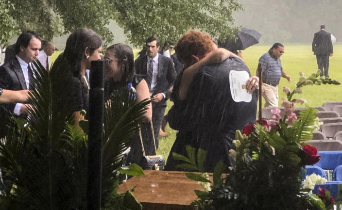 Buster Murdaugh, center, receives a hug in the rain during the funeral service for his brother, Paul, and mother, Maggie, on Friday, June 11, 2021 in Hampton, South Carolina. / Credit: Kacen Bayless/The Island Packet via AP
