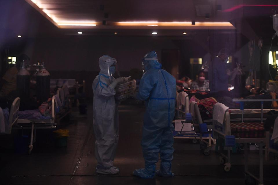 <p>Health workers wearing personal protective equipment (PPE) suits distribute food to Covid-19 coronavirus patients</p> (AFP via Getty Images)