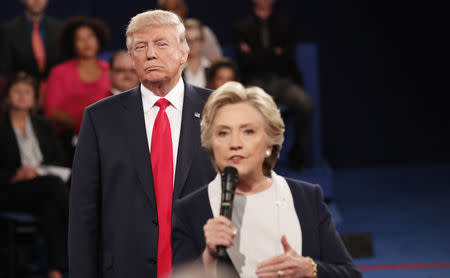 Republican U.S. presidential nominee Trump listens as Democratic nominee Clinton answers a question from the audience during their presidential town hall debate in St. Louis