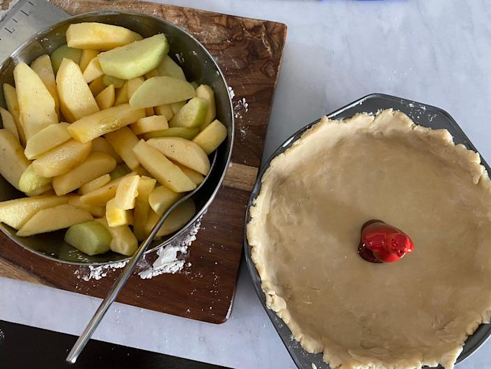 Apple slices next to an open pie crust.