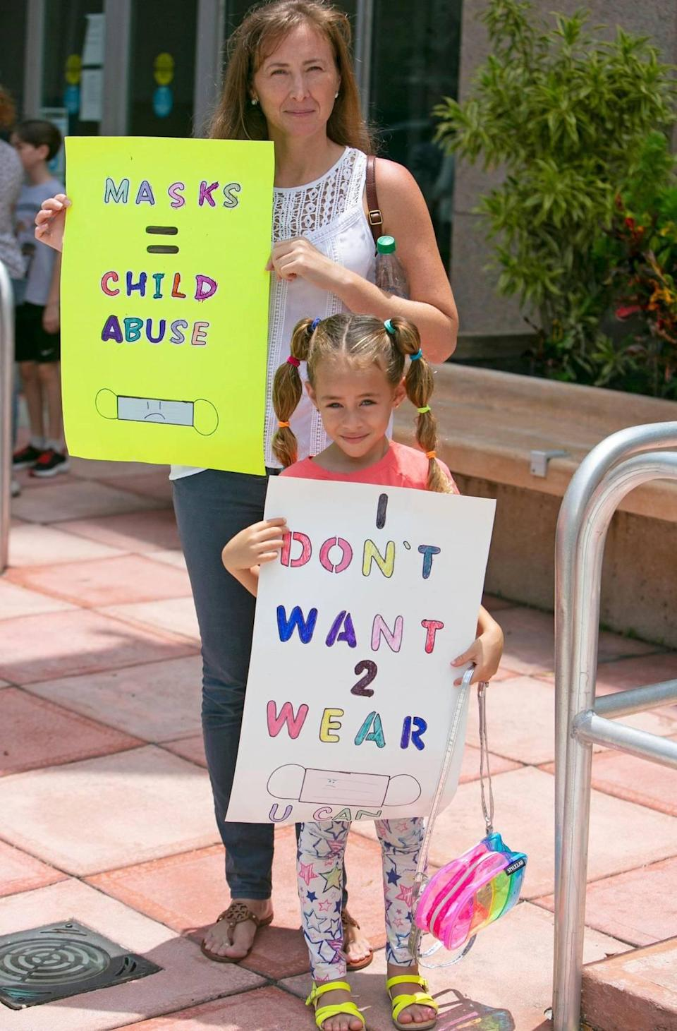 Barbara Rodas holds signs with her 6-year-old daughter, Athena Coletti, outside of the Kathleen C. Wright Administration Building of the Broward School Board in Fort Lauderdale, Tuesday, July 27, 2021. Athena was planning to speak in front of the School Board during a special workshop on COVID-19 safety precautions and potential mask mandates for the upcoming school year. The discussion was postponed until Wednesday after the anti-mask protesters refused to wear masks inside the room where the School Board was meeting.