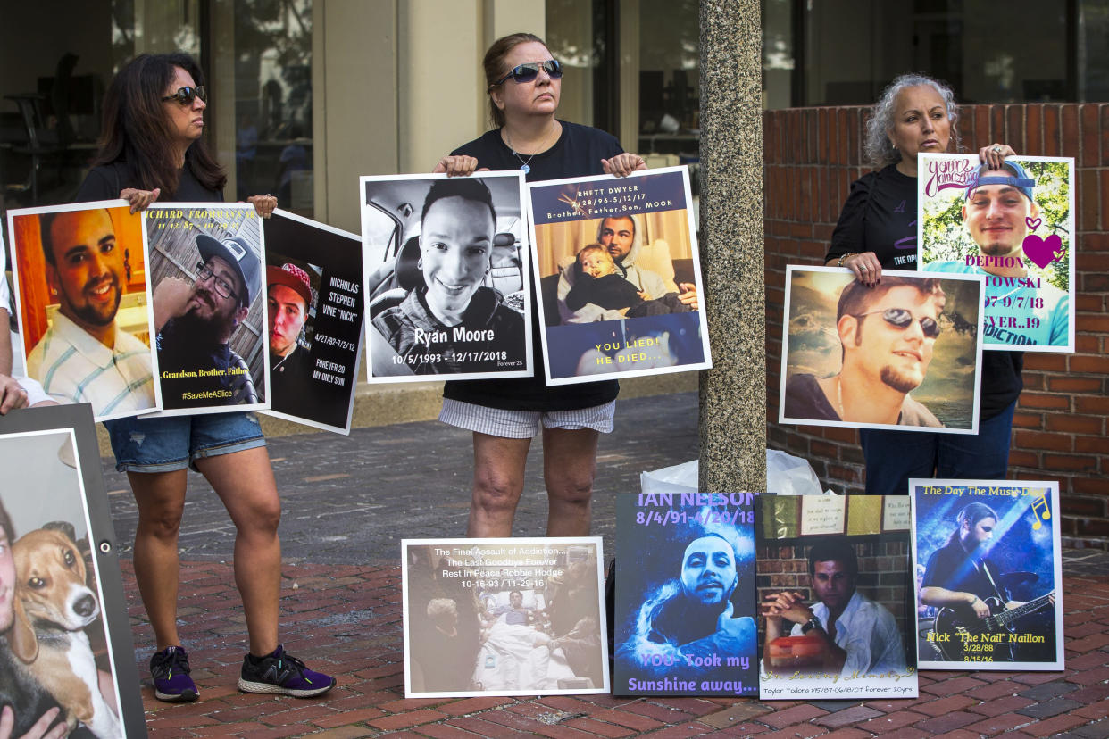 Protesters hold signs outside of the Suffolk County Superior Court in Boston on Aug. 2, 2019. Friends and family of opioid overdose victims gathered outside of the steps of the Suffolk County Superior Court while a lawsuit against Purdue Pharma was underway inside. (Photo by Nic Antaya for The Boston Globe via Getty Images)