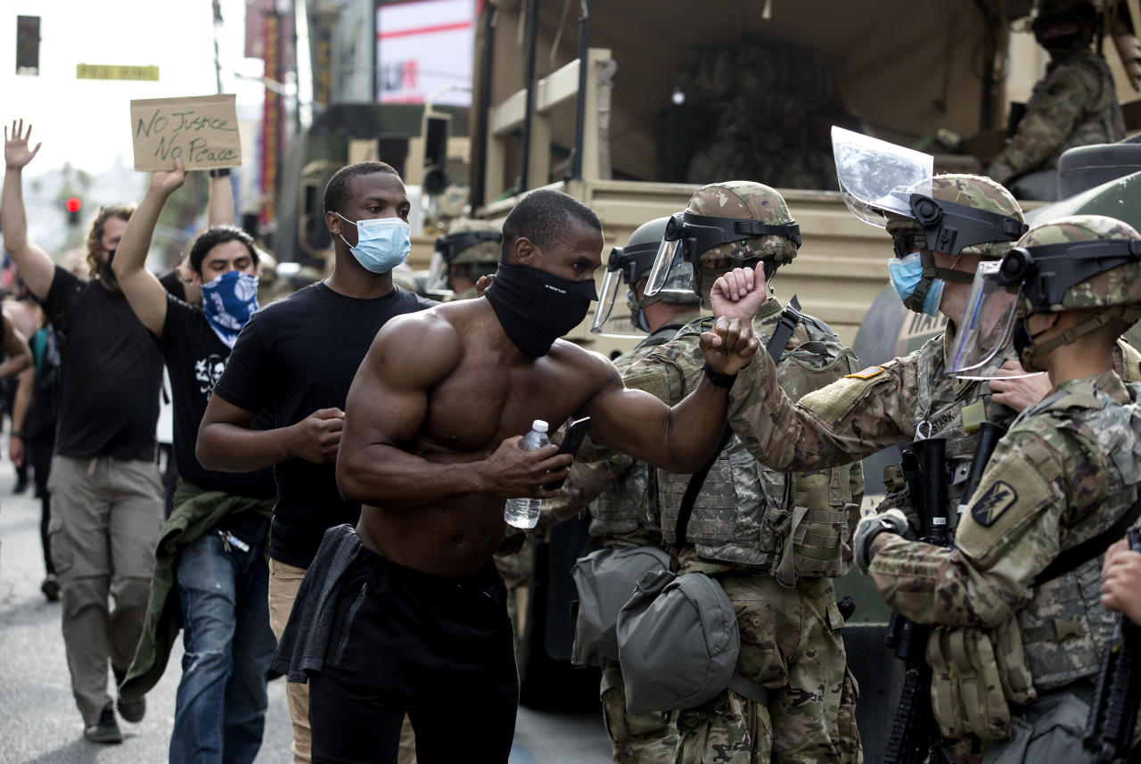 Demonstrators greet members of the National Guard as they march along Hollywood Boulevard, Tuesday, June 2, 2020, in the Hollywood section of Los Angeles, during a protest over the death of George Floyd, who died May 25 after he was restrained by Minneapolis police. (AP Photo/Ringo H.W. Chiu)