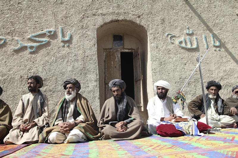 Afghan villagers listen to a speech by an Afghan official, unseen, part of a delegation during prayer ceremony for the victims of Sunday's killing of civilians by a U.S. soldier in Panjwai, Kandahar province south of Kabul, Afghanistan, Tuesday, March. 13, 2012. Taliban militants opened fire Tuesday on a delegation of senior Afghan officials including two of President Hamid Karzai's brothers visiting villages in southern Afghanistan where a U.S. soldier is suspected of killing 16 civilians. (AP Photo/Allauddin Khan)