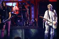 """<p>Kurt Cobain never seemed at ease with the whole MTV megafame thing, which was at its peak in 1992, one year after Nevermind came out and changed the music business in ways he probably never imagined or intended. So when Nirvana performed at that year's VMAs, Kurt was his typical rebellious self — starting their performance with a few politically incorrect bars of their unreleased and unrehearsed tune """"Rape Me"""" (against VMA producers' wishes) in one of the most chaotic and punk-rock appearances in MTV history. At the performance's conclusion, bandmate Krist Novoselic hurled his bass guitar in the air and tried to catch it, but it wacked him in the face instead. Krist blogged years later that Queen's Brian May had nursed him backstage with a glass of champagne, indicating that Krist had adjusted to the swishy MTV lifestyle much more easily than Kurt ever did. (Source: Getty Images) </p>"""