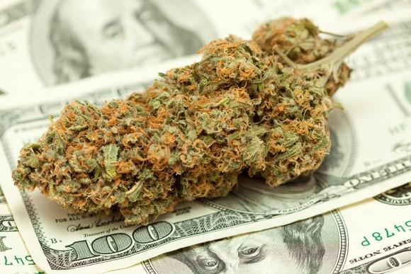 A cannabis bud atop a messy pile of hundred dollar bills.