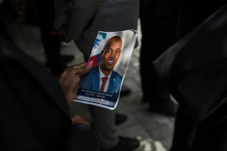 A guest holds a picture of late Haitian president Jovenel Moise during a ceremony in Port-au-Prince