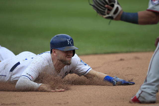 Kansas City Royals' Hunter Dozier slides into third base during the eighth inning of a baseball game against the Minnesota Twins at Kauffman Stadium in Kansas City, Mo., Sunday, Sept. 29, 2019. Dozier tripled on the play. (AP Photo/Orlin Wagner)