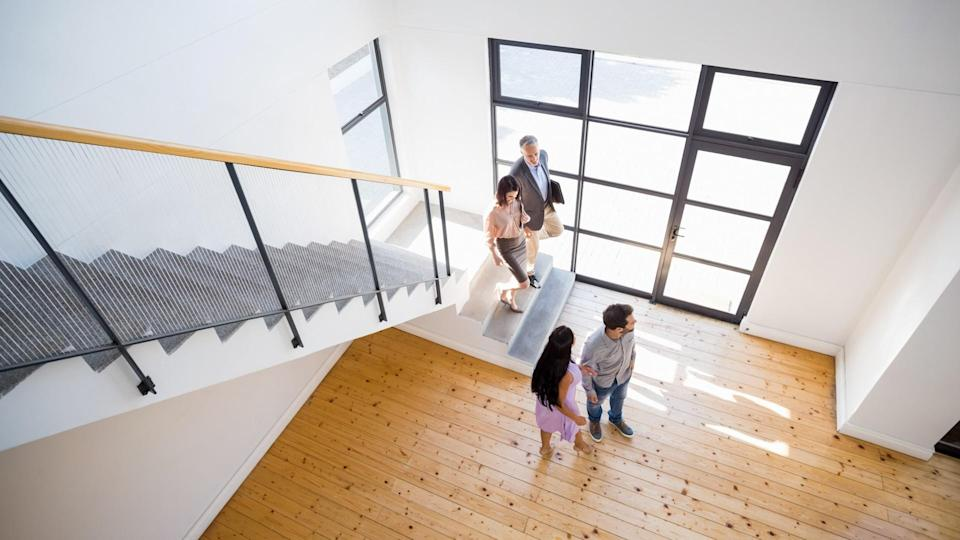 Real estate agent showing new house to couple - Image.