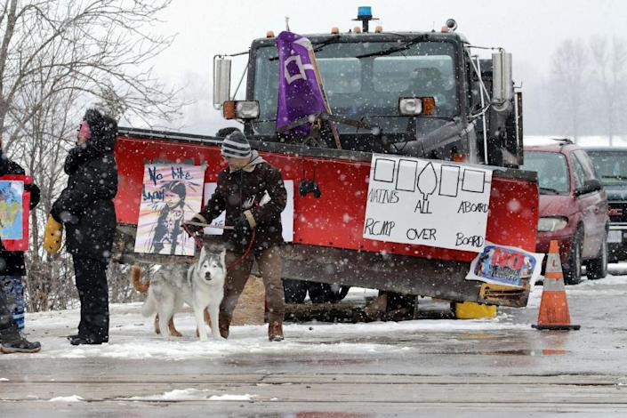 """<span class=""""element-image__caption"""">A man walks dogs across train tracks as members of the Tyendinaga Mohawk territory block the route servicing Via Rail, as part of a protest against British Columbia's Coastal GasLink pipeline, in Tyendinaga, Ontario, on Thursday.</span> <span class=""""element-image__credit"""">Photograph: Chris Helgren/Reuters</span>"""