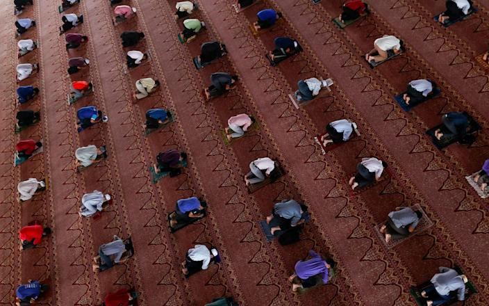 The faithful maintain social distance and wear protective face masks as they attend Friday prayer at a mosque in Putrajaya, outside Kuala Lumpur - FAZRY ISMAIL/EPA-EFE/Shutterstock