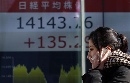 A pedestrian holding her mobile phone walks past an electronic board showing Japan's Nikkei average outside a brokerage in Tokyo February 5, 2014. REUTERS/Yuya Shino