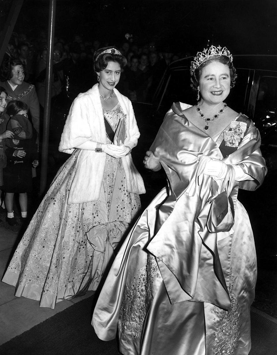 """<p>The true origins of Queen Mary's Sapphire Bandeau Tiara, seen here on Princess Margaret in 1958 attending a state banquet with the Queen Mother (who seemed to have borrowed Queen Elizabeth's George VI Demi-Parure for the occasion), are unknown. Some believe it came from the collection of Empress Marie Feodorovna while others contend Queen Mary had it commissioned herself. Though this tiara, whose center sapphire stone could be removed and switched out for other gems, looks very much like the <a href=""""https://www.townandcountrymag.com/style/jewelry-and-watches/a20756656/queen-mary-diamond-bandeau-tiara-meghan-markle-royal-wedding/"""" rel=""""nofollow noopener"""" target=""""_blank"""" data-ylk=""""slk:Queen Mary Diamond Bandeau Tiara"""" class=""""link rapid-noclick-resp"""">Queen Mary Diamond Bandeau Tiara</a> that Meghan Markle borrowed for her 2018 wedding to Prince Harry, they aren't the same piece. It's unclear what became of the Sapphire Bandeau.</p>"""