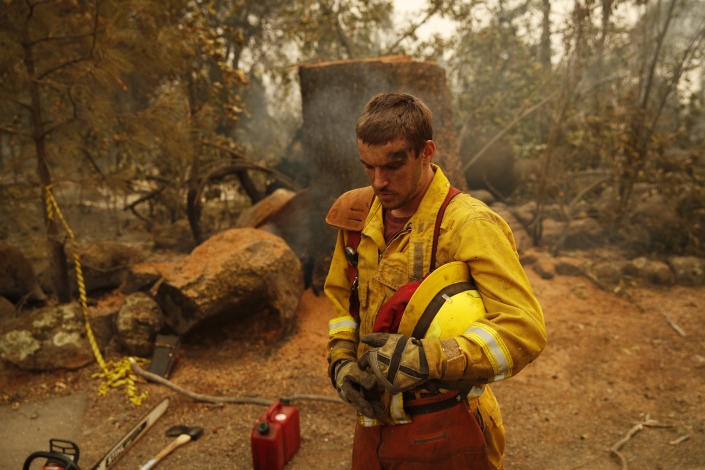 <p>Shawn Slack rests after felling trees burned in the Camp Fire on Monday in Paradise, Calif. (Photo: John Locher/AP) </p>