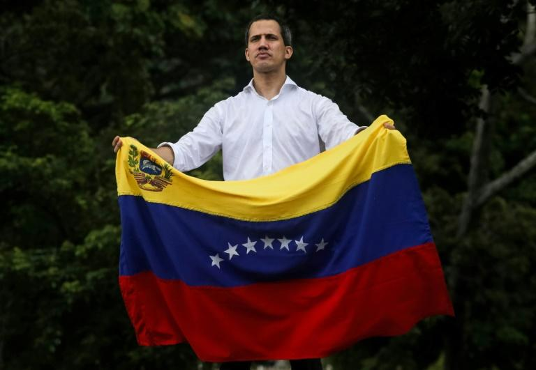 Venezuelan opposition leader Juan Guaido unfurls the country's flag during a rally in Caracas