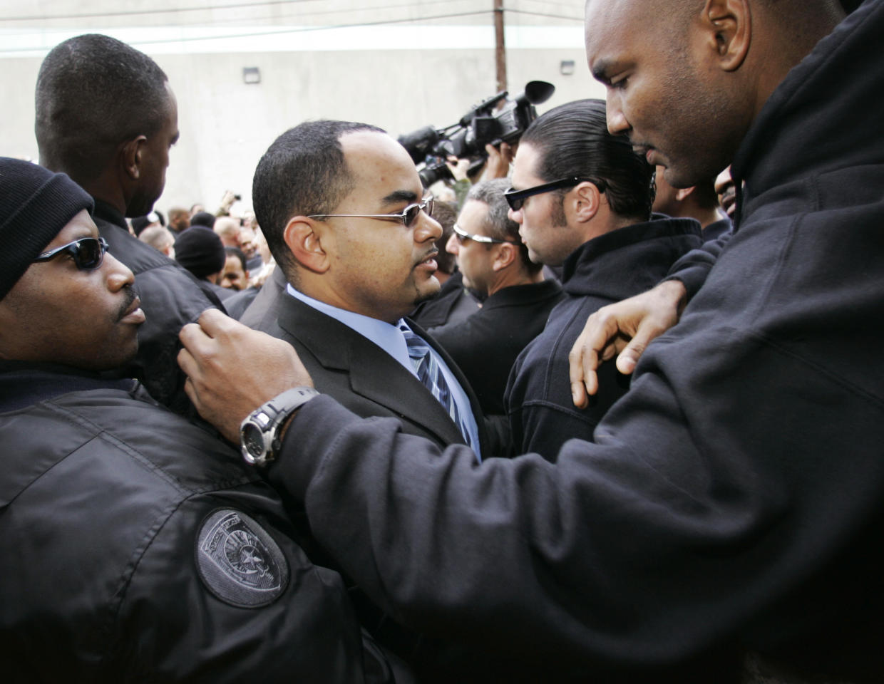 Anthony Villavaso II, third from left, hugs a fellow officer as he and six other New Orleans police officers turn themselves in at the city jail in New Orleans Tuesday, Jan. 2, 2007. Seven officers have been charged in connection with deadly shootings at the Danziger Bridge during the aftermath of Hurricane Katrina. (AP Photo/Alex Brandon)