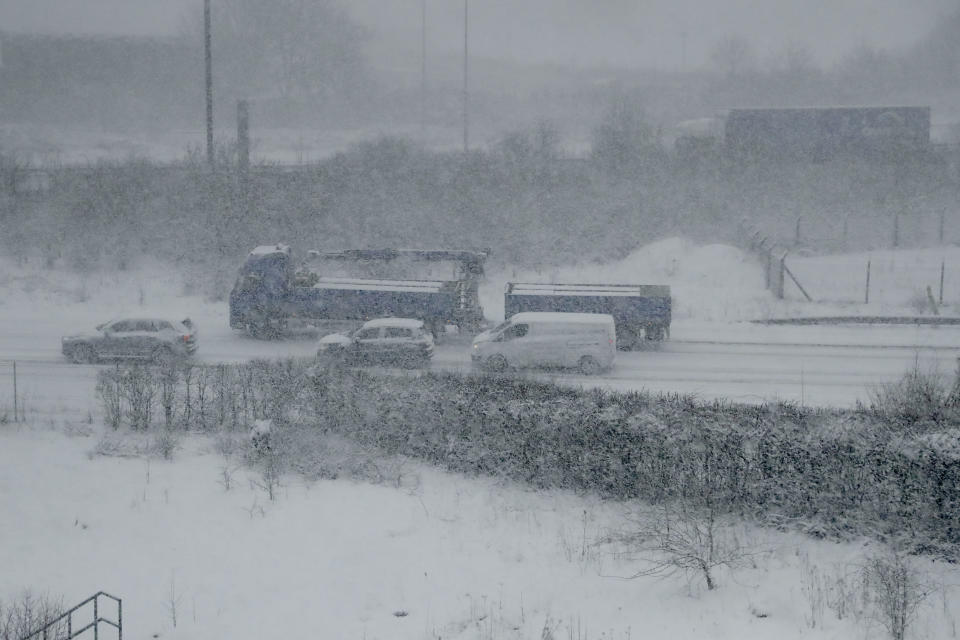 <p>Vehicles crawl along a road as snow falls in southeast England, as seen through the window of a train travelling from London to Canterbury. The Met Office said: 'Strong winds will lead to drifting of snow and severe wind chill, while lightning could be an additional hazard, particularly near coasts.' (AP Photo/Matt Dunham) </p>