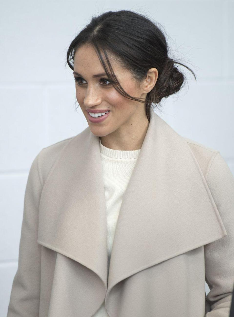 <p>Markle often prefers to style her hair in a messy bun for royal engagements. Two face-framing tendrils soften the look.</p>