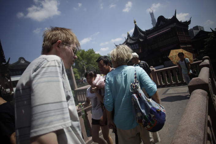 Foreign tourists visit Yuyuan Garden, one of the most famous tourist destinations in Shanghai, China, Tuesday, Aug. 13, 2013. China, one of the most visited countries in the world, has seen sharply fewer tourists this year — with worsening air pollution partly to blame. (AP Photo/Eugene Hoshiko)