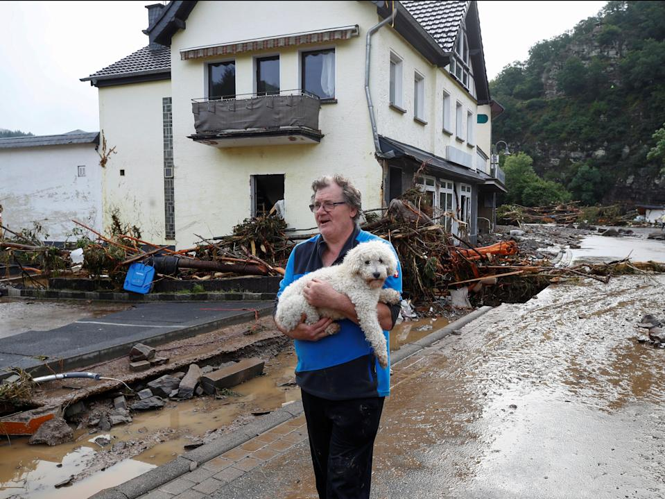 A man carries a dog through the debris brought on by the flooding in Schuld, Germany (Wolfgang Rattay/Reuters)