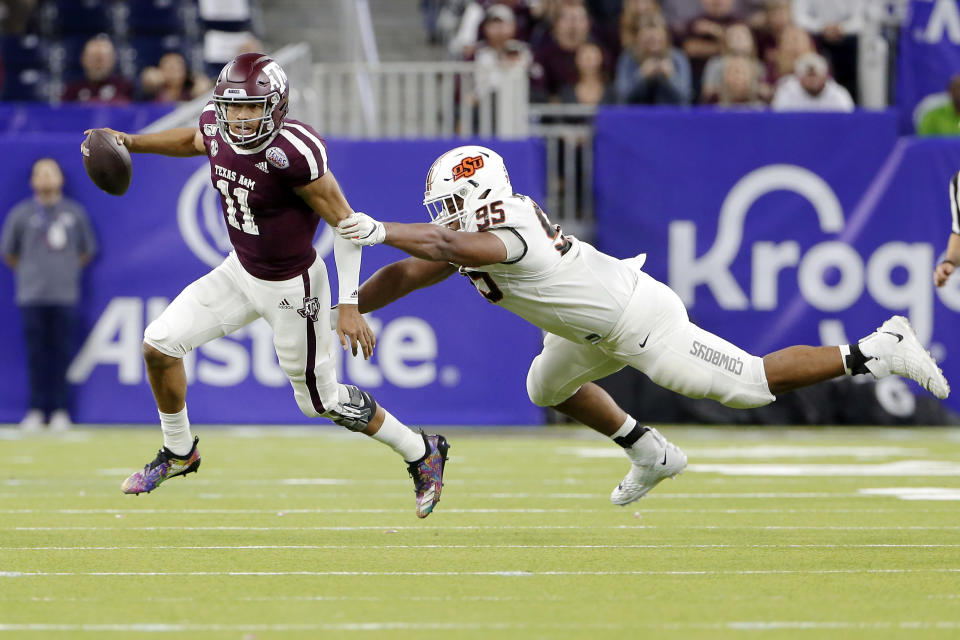 Texas A&M quarterback Kellen Mond (11) slips the tackle attempt by Oklahoma State defensive tackle Israel Antwine (95) during the second half of the Texas Bowl NCAA college football game Friday, Dec. 27, 2019, in Houston. (AP Photo/Michael Wyke)