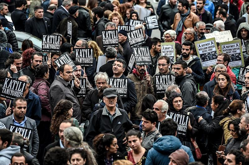 """Protesters hold placards that read """"We know the killer"""" as Turkish riot police block the road on October 13, 2015 in Istanbul during a demonstration against the deadly attacks in Ankara (AFP Photo/Ozan Kose)"""